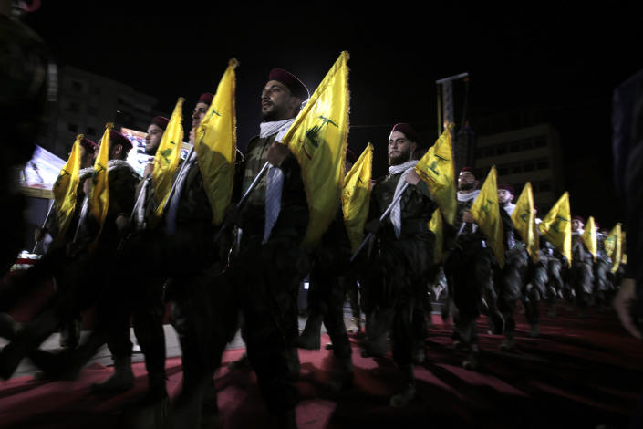 FILE - In this May 31, 2019 file photo, Hezbollah fighters march at a rally to mark Jerusalem day, in the southern Beirut suburb of Dahiyeh, Lebanon. As Lebanon sinks deeper into poverty and collapse, many Lebanese are more openly criticizing the Iran-backed Hezbollah, blaming it for its role in the devastating, multiple crises plaguing the country. This includes a dramatic currency crash and severe shortages in medicines and fuel that has paralyzed the country. (AP Photo/Hassan Ammar, File)