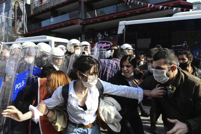 Turkish police officers, in riot gear, and wearing face masks for protections against the spread of the coronavirus, scuffle with protesters during a demonstration in Istanbul, Tuesday, June 2, 2020, against the recent killing of George Floyd in Minneapolis. (AP Photo/Omer Kuscu)