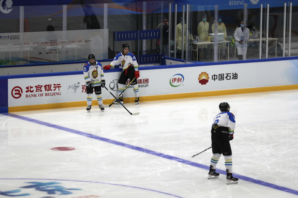 Medical workers wearing face masks watch Capital Institute hockey team players practice at the ice hockey venue set for the 2022 Beijing Winter Olympics at the National Indoor Stadium in Beijing, Thursday, April 1, 2021. Chinese capital holds 10 days test events for 2022 Beijing Winter Olympics in five different venues from April 1-10 and becomes the first city to hold both the Winter and Summer Olympics. (AP Photo/Andy Wong)