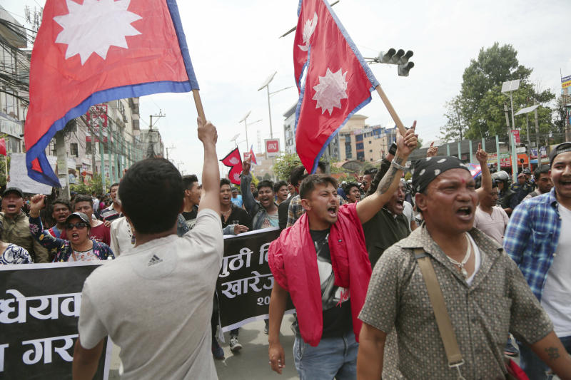 Nepalese Newar community people shout slogans during a protest against government in Kathmandu, Nepal, Wednesday, June 19, 2019. Thousands of people protested in the Nepalese capital to protest a Bill that would give government control over community and religious trusts. Protesters demanded the government scrap the proposed Bill to protect these trusts that hold religious ceremonies and festivals. (AP Photo/Niranjan Shrestha)