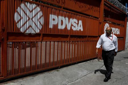 A man walks past a gate with the corporate logo of the state oil company PDVSA in Caracas