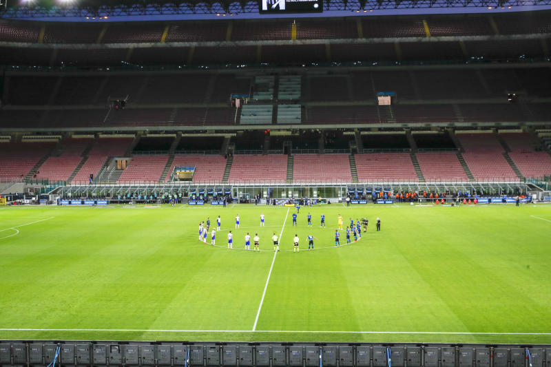 Players observe a minute of silence to honor the victims of coronavirus, prior to the start of the Serie A soccer match between Inter Milan and Sampdoria at the San Siro Stadium, in Milan, Italy, Sunday, June 21, 2020. (AP Photo/Antonio Calanni)