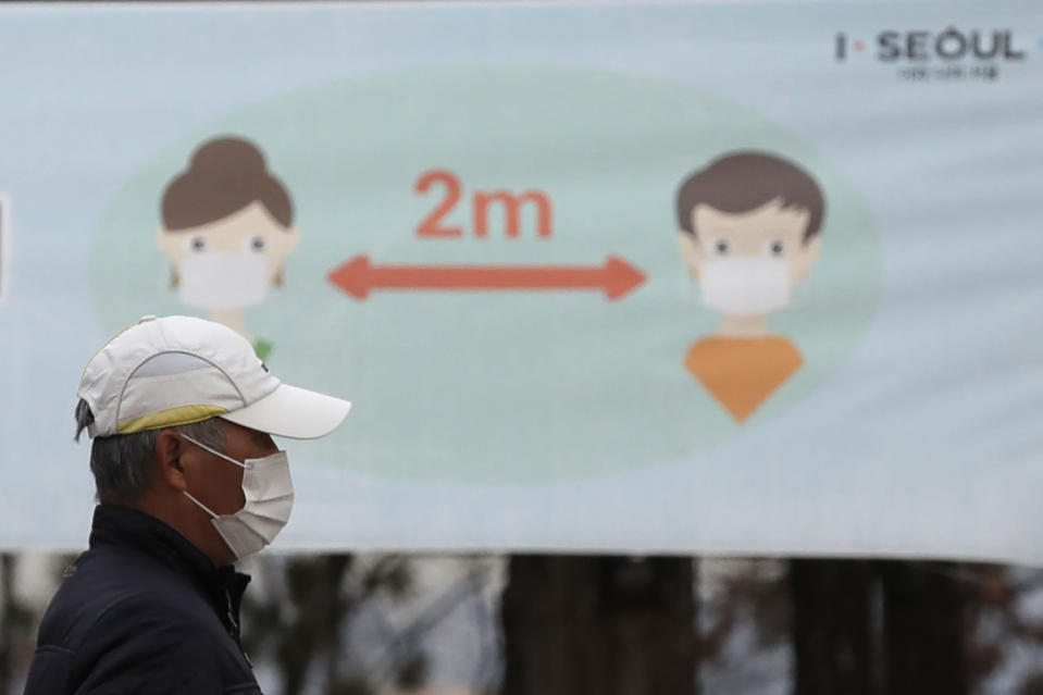A man wearing a face mask as a precaution against the coronavirus walks past a banner showing social distancing at a park in Seoul, South Korea, Tuesday, Nov. 24, 2020. Authorities in the South Korean capital on Monday announced a tightening of social distancing regulations, including shutting nightclubs, limiting service hours at restaurants and reducing public transportation. (AP Photo/Lee Jin-man)