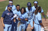 Members of the Toronto Blue Jays celebrate with Bo Bichette, center, after his game-winning home run against the New York Yankees during the ninth inning of a baseball game Wednesday, April 14, 2021, in Dunedin, Fla. The Blue Jays won 5-4. (AP Photo/Mike Carlson)