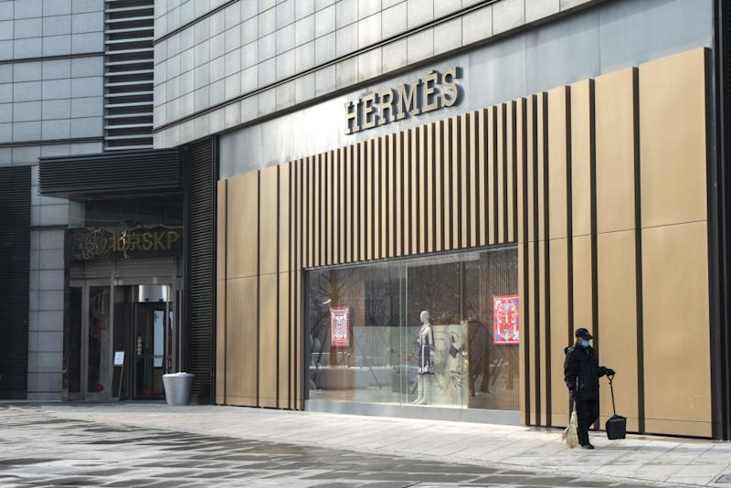 A cleaner walks past an Hermes International SCA store in Beijing, China, on Sunday, Feb. 2, 2020. (Photographer: Giulia Marchi/Bloomberg)