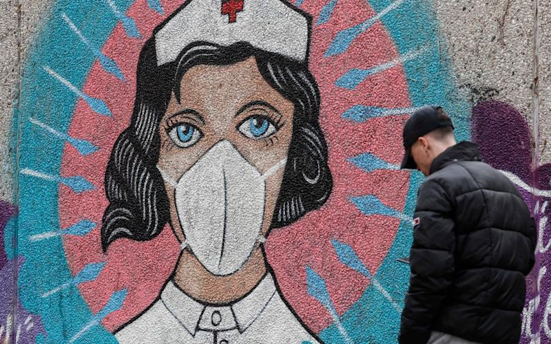 A man passes a graffiti by street artist 'Uzey', depicting a nurse as superhero in the coronavirus pandemic on a wall in Hamm, Germany - AP