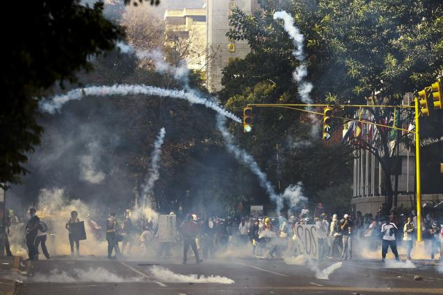 Anti-government protesters run from tear gas during a protest in Caracas March 8, 2014. Latin American foreign ministers will meet next week to discuss the unrest in Venezuela that has left at least 20 dead and convulsed the South American OPEC nation, diplomatic sources said on Friday. REUTERS/Carlos Garcia Rawlins (VENEZUELA - Tags: POLITICS CIVIL UNREST)