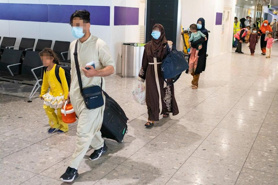Afghan refugees head to the processing facility after arriving on a flight to Heathrow (Dominic Lipinski/PA) (PA Wire)