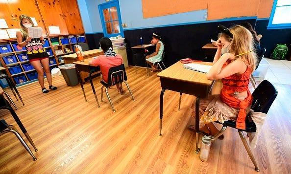 Instructor Amy Giang teaches a class of fourth through seventh graders, wearing masks and spaced apart per coronavirus guidelines, during summer school sessions July 9 at Happy Day School in Monterey Park, California.