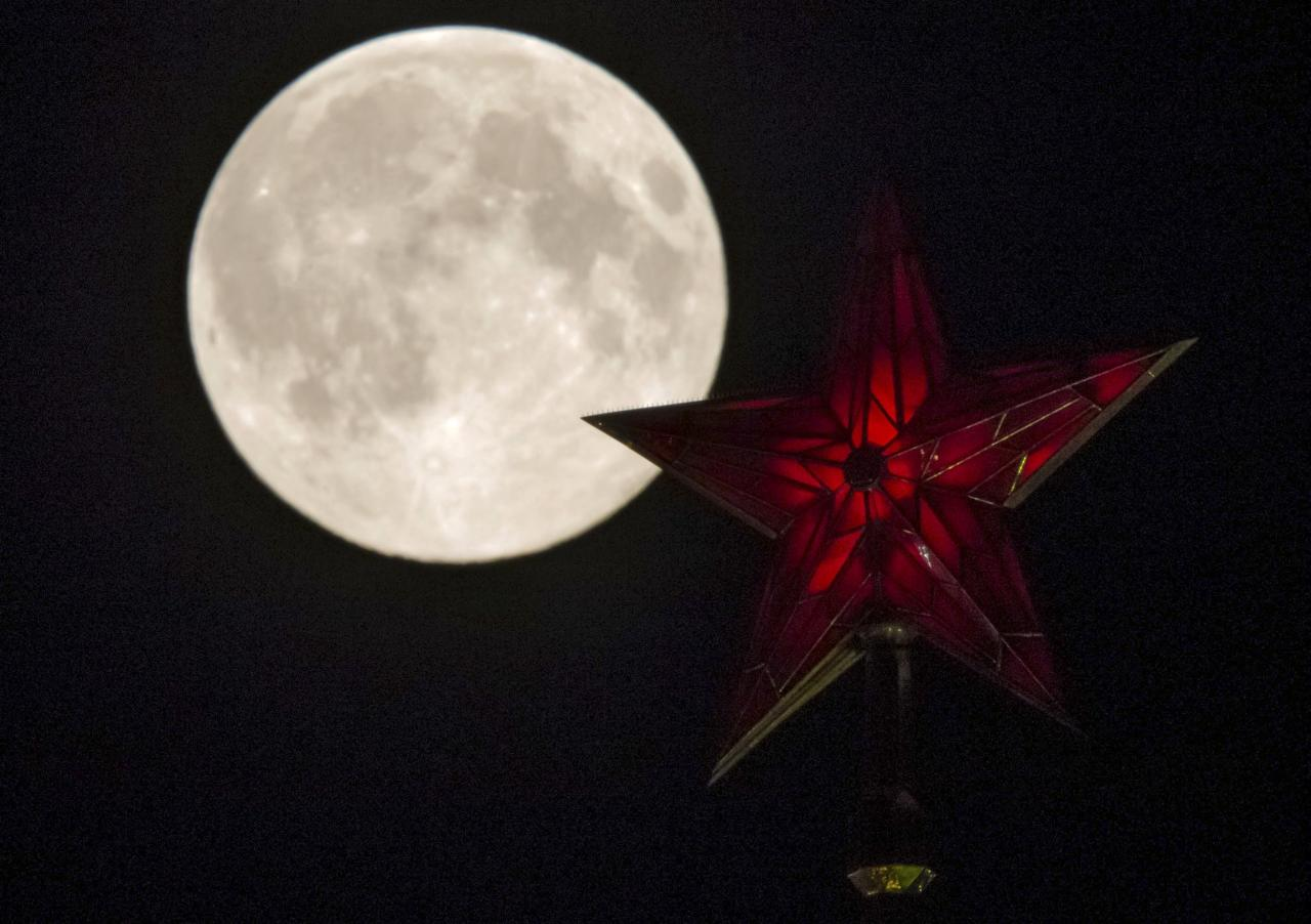 The supermoon rises over the stars of Moscow's Kremlin towers in Moscow August 10, 2014. Occurring when a full moon or new moon coincides with the closest approach the moon makes to the Earth, the Supermoon results in a larger-than-usual appearance of the lunar disk. REUTERS/Maxim Shemetov (RUSSIA - Tags: ENVIRONMENT)