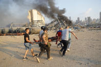 Civilians carry a person at the explosion scene that hit the seaport, in Beirut Lebanon, Tuesday, Aug. 4, 2020. (AP Photo/Hussein Malla)
