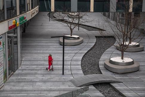 A child with a protective mask riding on a scooter in a deserted shopping centre in Beijing's Sanlitun on 26 February 2020, on what should otherwise be a bustling week day in one of the busiest areas of the Chinese capital. Photo: EPA-EFE