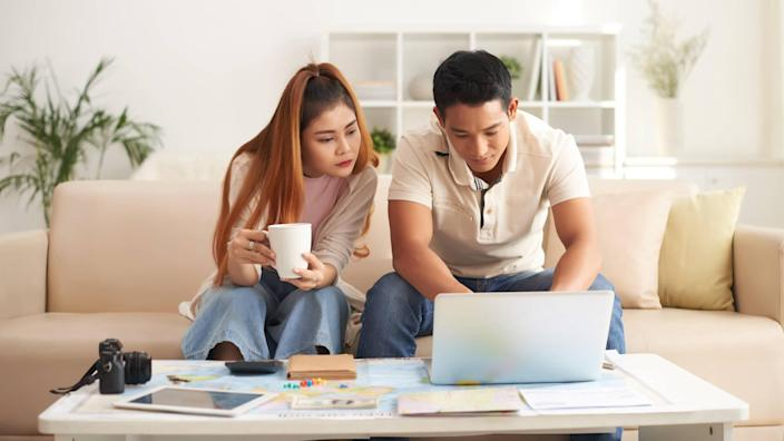 Portrait of couple on computer, fees, America, money, payment, avoid fees, bills, debt