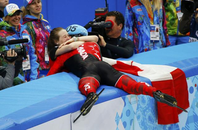 Winner Canada's Charles Hamelin hugs his girlfriend and compatriot speed skater Marianne St-Gelais after the men's 1,500 metres short track speed skating race finals at the Iceberg Skating Palace during the 2014 Sochi Winter Olympics February 10, 2014. REUTERS/Brian Snyder (RUSSIA - Tags: OLYMPICS SPORT SPEED SKATING)