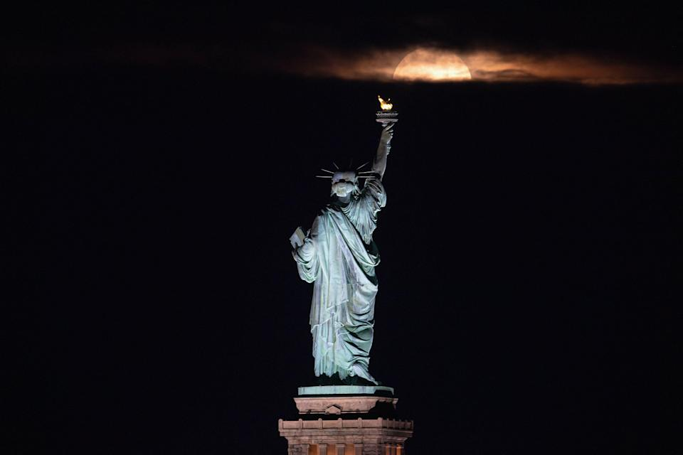 The full moon, known as the strawberry moon, rises behind the Statue of Liberty in New York City on June 24, 2021. The first full moon of summer 2021, also known as the Strawberry Moon, rises June 24, marking the last supermoon of the year. June's full moon is often referred to as the Strawberry Moon because it falls during the strawberry harvesting season in the northeastern U.S.