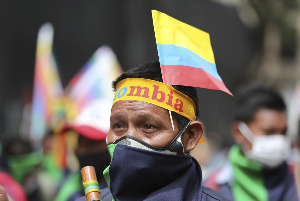 An Indigenous man marches against the government's handling of a wide range of issues including the economic fallout of the pandemic and implementation of the peace accord, in Bogota, Colombia, Wednesday, Oct. 21, 2020. Indigenous leaders, students and union members gathered in Plaza Bolivar waving flags and banners decrying the government nearly one year after massive protests rocked the country only to fizzle with little to show by way of reform. (AP Photo/Fernando Vergara)