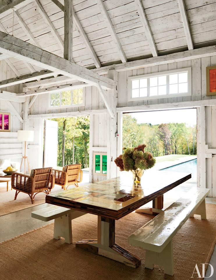 """A barn serves as the poolhouse at <a rel=""""nofollow"""" href=""""http://www.architecturaldigest.com/story/india-mahdavi-litchfield-county-connecticut-home-article?mbid=synd_yahoo_rss"""">a Connecticut home</a> decorated by India Mahdavi; the dining table and benches are by Piet Hein Eek."""