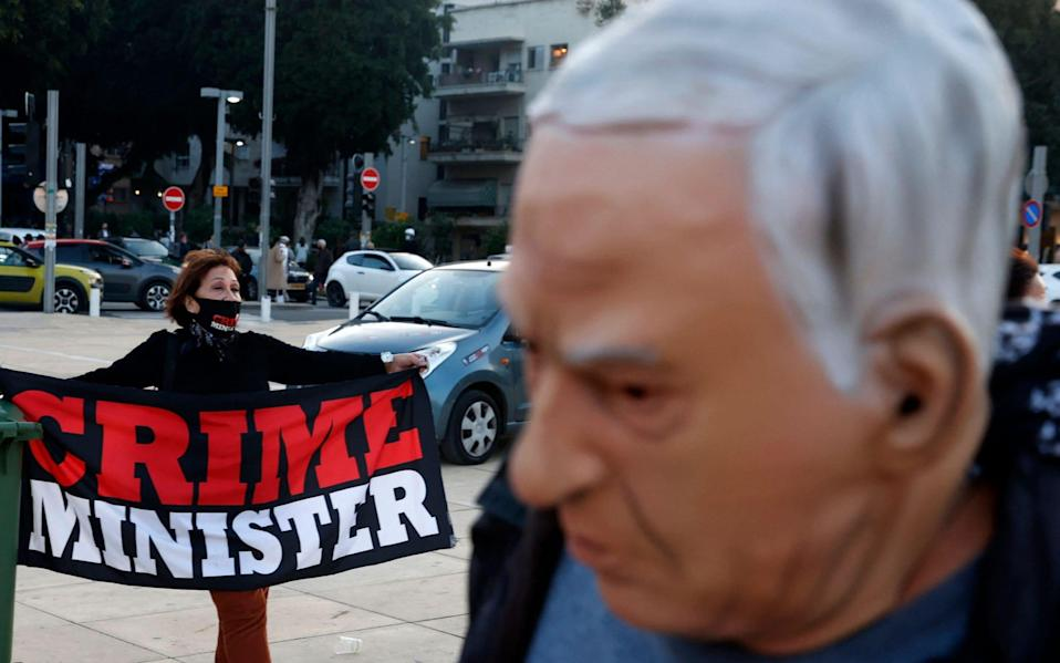 An Israeli disguised as Prime Minister Benjamin Netanyahu, walks past a fellow protester during a rally against the premier  - Jack Guez/AFP