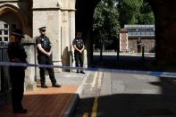 Police officers stand observing minute's silence near to the scene of reported multiple stabbings in Reading