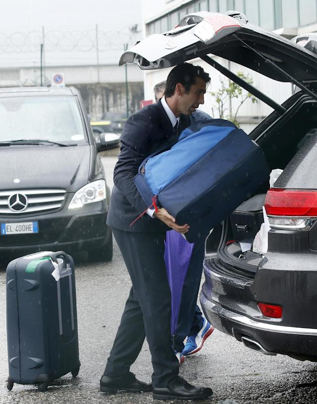 Italy goalkeeper Gianluigi Buffon loads his luggage onto a car upon his arrival with his teammates at Malpensa airport after landing from Brazil, in Milan, Italy, Thursday, June 26, 2014. Italy was disqualified from the World Cup after loosing to Uruguay in their group stage round. (AP Photo/Luca Bruno)