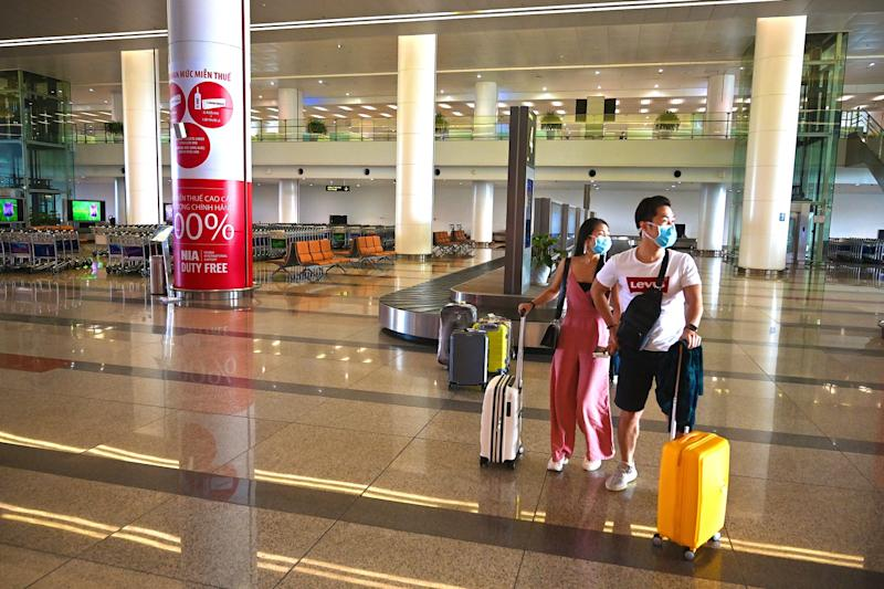 Passengers with protective facemasks walk with their luggage in the empty arrival hall of Noi Bai International Airport in Hanoi on February 27, 2020, as the number of air travellers has plummeted amid fears over the spread of the COVID 19 coronavir