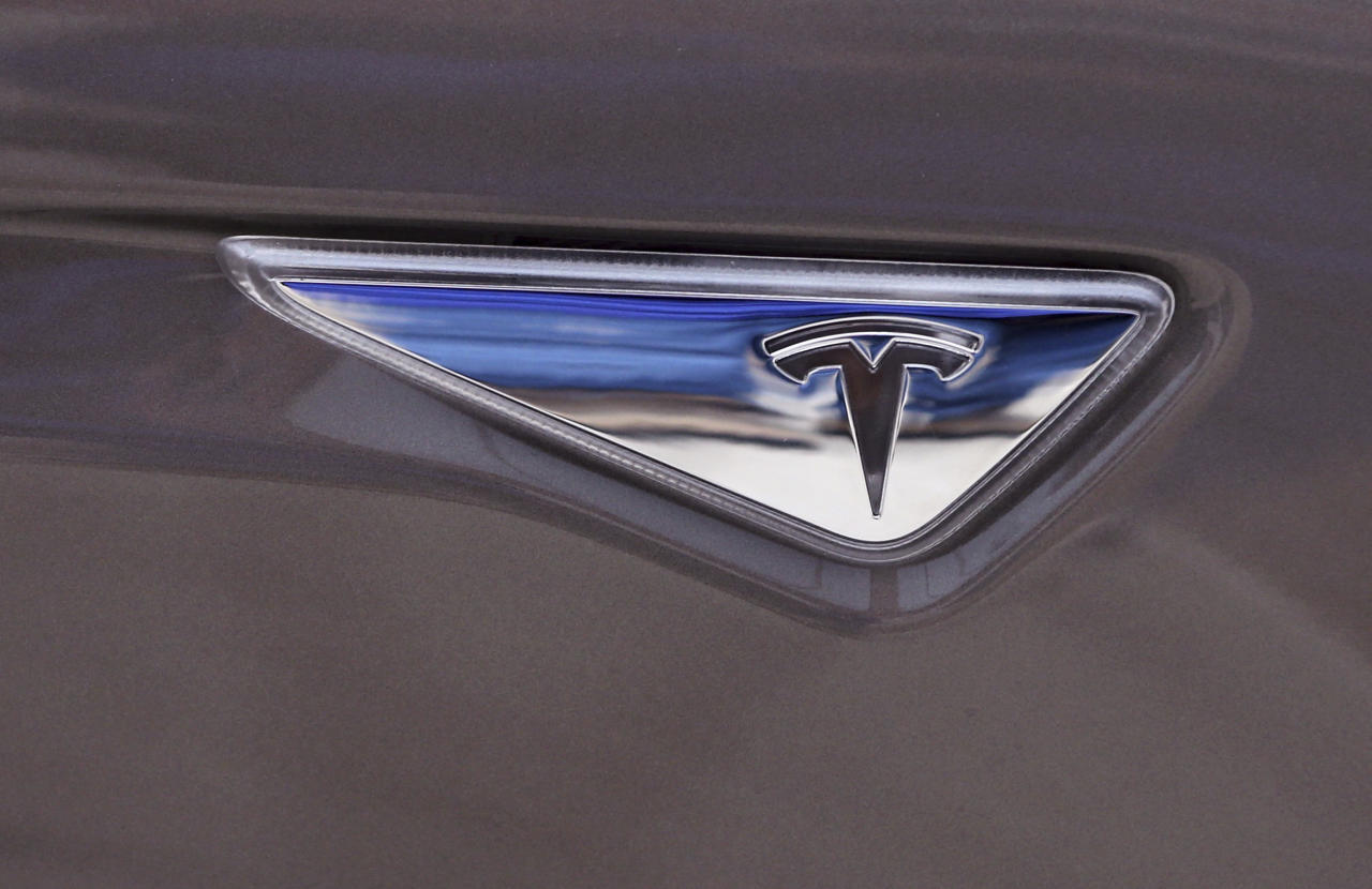 FILE - This April 7, 2015 file photo shows the Tesla logo on the new Tesla Model S 70D during a test drive in Detroit. Tesla says it's put together a 10-year compensation package for CEO Elon Musk that pays him based on certain market cap and operational milestones he hits - otherwise he gets nothing. The electric vehicle maker says Tuesday, Jan. 23, 2018, its market cap would have to grow to $650B for Musk to fully vest. (AP Photo/Carlos Osorio, File)