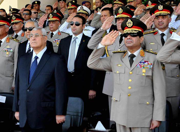 FILE - In this July 22, 2013, file photo released by the Egyptian Presidency, Egypt's interim President Adly Mansour, left, standing next to Defense Minister Gen. Abdel-Fattah el-Sissi, listens to the national anthem during a medal ceremony at a military base east of Cairo. The head of Egypt's military, Abdel-Fattah el-Sissi, is riding on a wave of popular fervor that is almost certain to carry him to election as president. Unknown only two years ago, a broad sector of Egyptians now hail him as the nation's savior after he ousted the Islamists from power, and the state-backed personality cult around him is so eclipsing, it may be difficult to find a candidate to oppose him if he runs. Still, if he becomes president, he faces the tough job of ruling a deeply divided nation that has already turned against two leaders.(AP Photo/Sheriff Abd El Minoem, Egyptian Presidency, File)