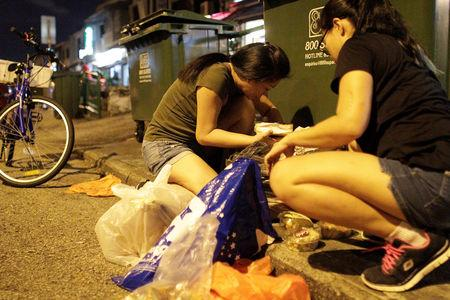 Freegans, who wish to remain anonymous, look through trash bags from a bin while dumpster diving in Singapore November 14, 2018. Picture taken November 14, 2018. REUTERS/Natashia Lee