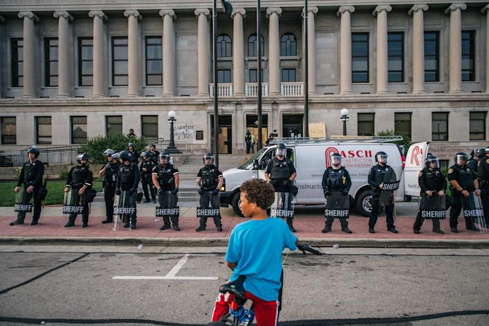 "A boy on his bike in front of law-enforcement officials outside the Kenosha County Courthouse on Monday. Officials were deployed to protect the courthouse amid the civil unrest after Blake's shooting. <p class=""copyright""><a href=""https://www.gettyimages.com/detail/news-photo/boy-sits-on-his-bike-in-front-of-law-enforcement-at-the-news-photo/1228192133?adppopup=true"" rel=""nofollow noopener"" target=""_blank"" data-ylk=""slk:Brandon Bell/Getty Images"" class=""link rapid-noclick-resp"">Brandon Bell/Getty Images</a></p>"