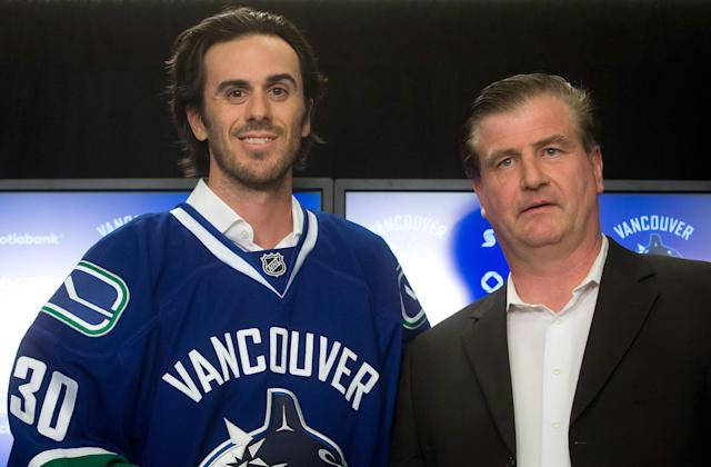 Vancouver Canucks' goalie Ryan Miller, left, stands for photos with general manager Jim Benning after Miller signed a three-year contract with the NHL hockey team, Tuesday, July 1, 2014 in Vancouver, British Columbia. (AP Photo/The Canadian Press, Darryl Dyck)
