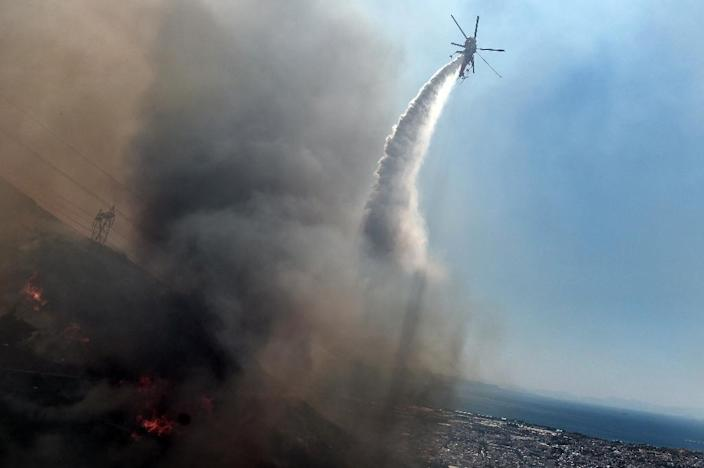 A fire fighting helicopter sprays water on a fire in Athens on July 17, 2015 (AFP Photo/Aris Messinis)