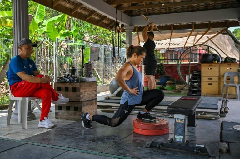 """""""If I didn't have Team HD, I admit I wouldn't be here, I would have gone home to the Philippines,"""" says Hidilyn Diaz, seen here working out in her makeshift gym in a car port in Malaysia under the watchful eye of Chinese coach Gao Kaiwen (left)"""