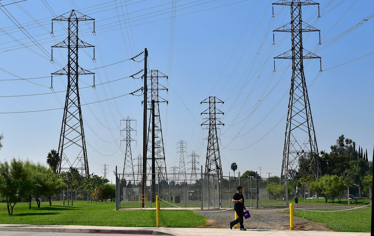 A pedestrian walks past a row of power lines in Rosemead, California, on October 9, as southern California braces for potentially widespread power outages. (Photo by Frederic J. BROWN / AFP) (Photo by FREDERIC J. BROWN/AFP via Getty Images) (Photo: FREDERIC J. BROWN via Getty Images)