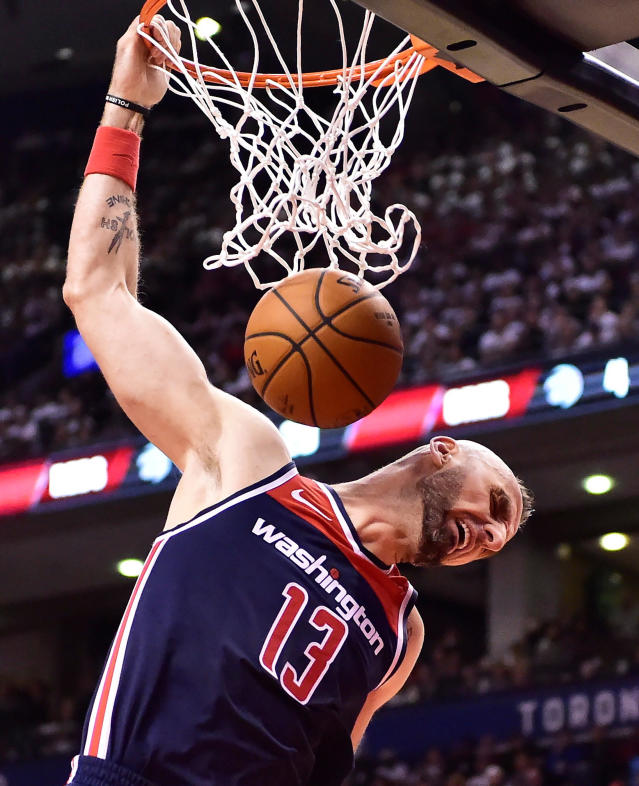 FILE - In this April 14, 2018, file photo, Washington Wizards center Marcin Gortat dunks against the Toronto Raptors during the second half of Game 1 of an NBA basketball first-round playoff series in Toronto. The NBA will return to London next year with a regular-season game between the Washington Wizards and the New York Knicks. International players on the rosters include Gortat, of Poland. (Frank Gunn/The Canadian Press via AP, File)