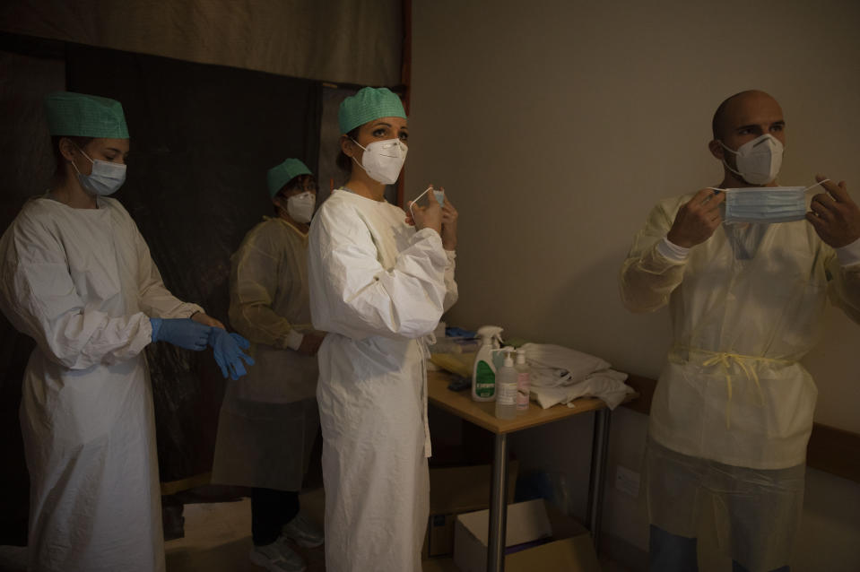 Belgian Army healthcare workers and supervisory personnel suit up prior to doing their rounds in the COVID-19 ward of the CHC nursing home in Landenne, Belgium, Wednesday, Nov. 4, 2020. Belgium, proportionally still the worst-hit nation in Europe when it comes to coronavirus cases, said Wednesday that there were increasing signs of that a turning point in the crisis was drawing close. The Belgian Army has been deployed to help several hard hit areas in the country. (AP Photo/Virginia Mayo)