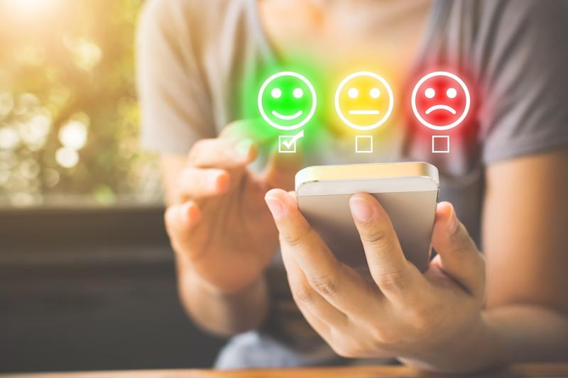 Customer Service Experience and Business Satisfaction Survey. Woman choose face smile on smart phone