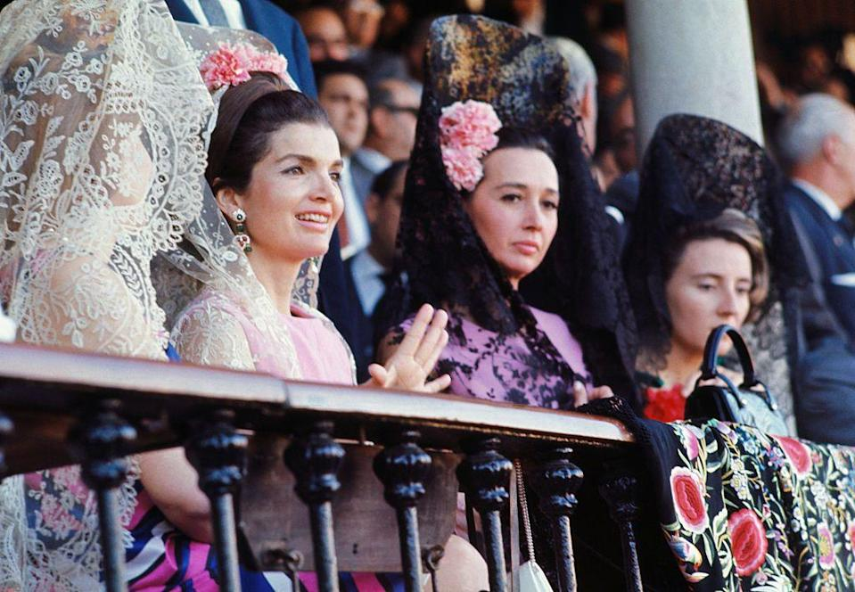 <p>Jackie Kennedy wears a white lace Mantillas while at a bullfight in Seville, Spain with the Duchess of Alba. </p>
