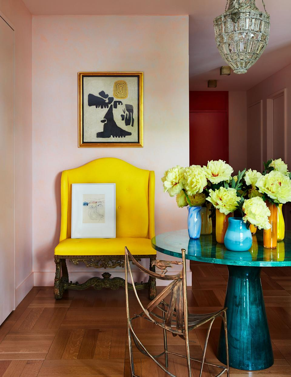 """<div class=""""caption""""> <a href=""""https://www.benjaminmoore.com/en-us"""" rel=""""nofollow noopener"""" target=""""_blank"""" data-ylk=""""slk:Benjamin Moore"""" class=""""link rapid-noclick-resp"""">Benjamin Moore</a> shades of pink and red warm the entrance hall, where a 1970s Aldo Tura table centers the vestibule; Claude Lalanne chair, antique Italian bench, Willi Baumeister painting. </div> <cite class=""""credit"""">Stephen Kent Johnson </cite>"""