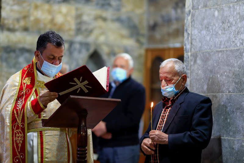 A priest Father Ammar Altony Yako leads the prayers as Iraqi Christians attend a mass at the Grand Immaculate old Church in Qaraqosh