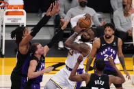 Los Angeles Lakers forward LeBron James, center, tries to shoot as Toronto Raptors forward Freddie Gillespie, left, guard Malachi Flynn, second from left, guard Rodney Hood, second from right, and center Khem Birch defend during the first half of an NBA basketball game Sunday, May 2, 2021, in Los Angeles. (AP Photo/Mark J. Terrill)