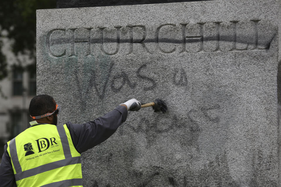 A worker cleans graffiti from the plinth of the statue of Sir Winston Churchill at Parliament Square in London, following a Black Lives Matter protest at the weekend, Monday June 8, 2020 as people protested against the killing of George Floyd by police officers in Minneapolis, USA. (Aaron Chown/PA via AP)