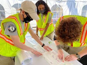 A team of AmeriCorps members serving with the National Civilian Community Corps creates signage to be used within a vaccination center at the Miami-Dade Community College North Campus.