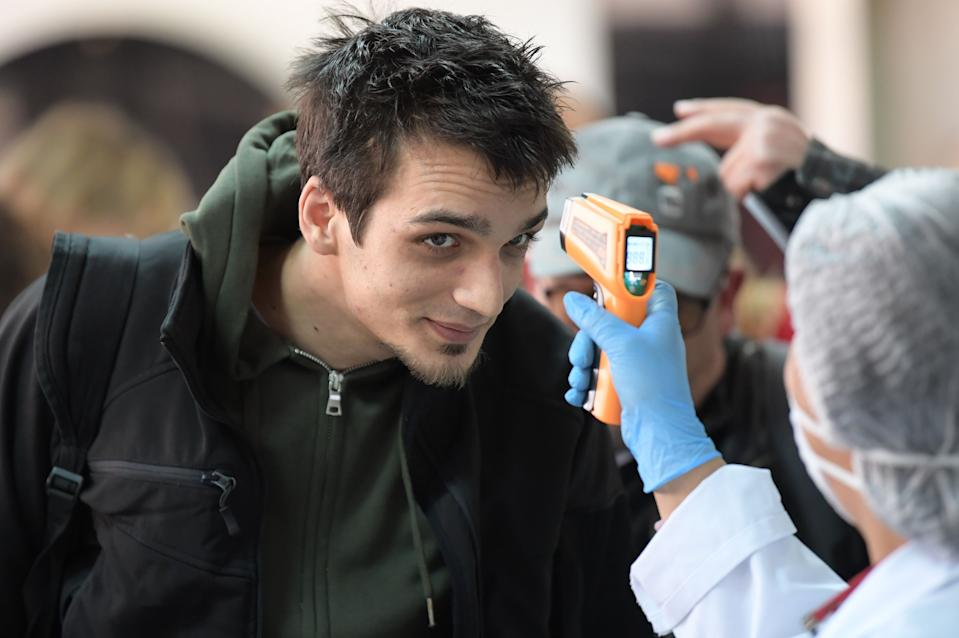 A health personnel checks the temperature of passengers upon their arrival at Tunis-Carthage Airport in the Tunisian capital Tunis on March 10, 2020. (Photo by FETHI BELAID / AFP) (Photo by FETHI BELAID/AFP via Getty Images)