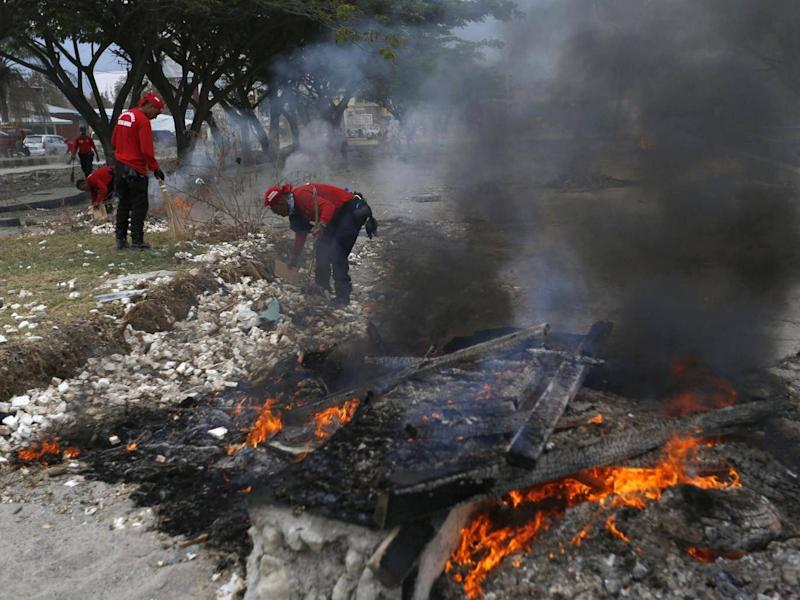Rescuers burn debris (Associated Press)