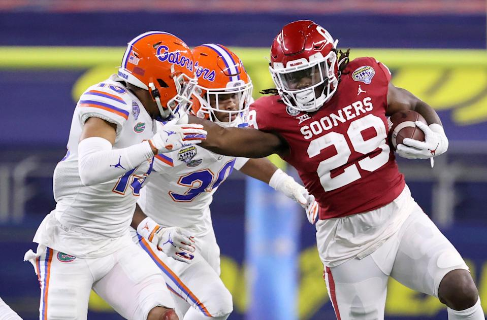 Oklahoma Sooners running back Rhamondre Stevenson (29) stiff arms Florida Gators defensive back Donovan Stiner (13) .