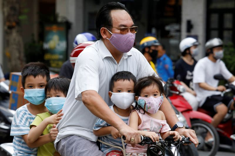 A man and his children, all wearing protective masks, ride a bicycle on a street in Hanoi