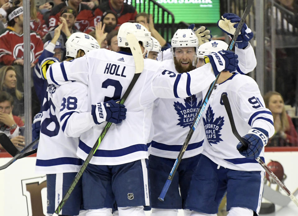 Toronto Maple Leafs' William Nylander (88), Justin Holl (3), Jake Muzzin (8) and John Tavares (91) surround Ilya Mikheyev to celebrate his goal during the first period of an NHL hockey game against the New Jersey Devils, Friday, Dec. 27, 2019, in Newark, N.J. (AP Photo/Bill Kostroun)
