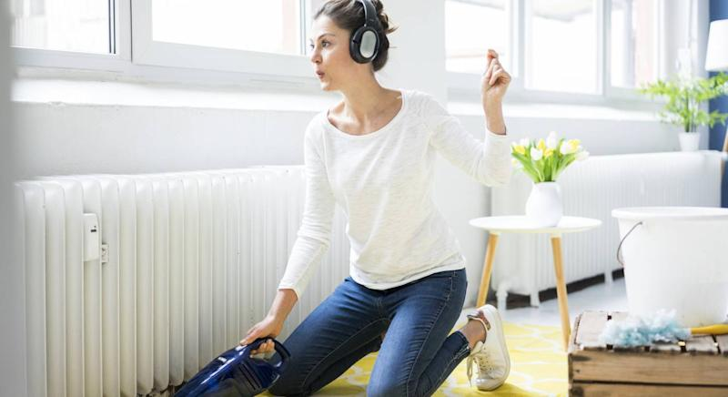 Woman cleaning her house while listening to music [Photo: Getty]