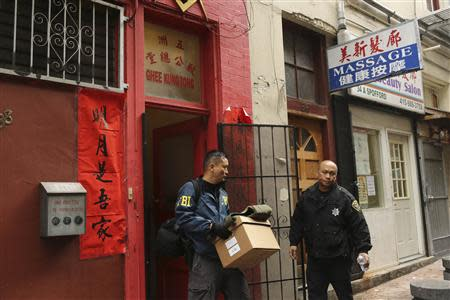 An agent with the U.S. Federal Bureau of Investigation (FBI) removes boxes from the Ghee Kung Tong building, which houses the Chinese Freemasons, in the Chinatown neighborhood in San Francisco, California March 26, 2014. REUTERS/Robert Galbraith