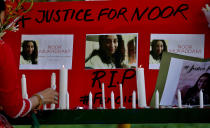 A women's rights activist places a candle beside a poster with the pictures of Noor Mukadam, who was recently beheaded, during a candle light vigil to pay tribute to Noor and other domestic violence victims, in Islamabad, Pakistan, Sunday, July 25, 2021. The killing of Mukadam in an upscale neighborhood of Pakistan's capital has shone a spotlight on the relentless violence against women in the country. Rights activists say such gender-based assaults are on the rise as Pakistan barrels toward greater religious extremism. (AP Photo/Anjum Naveed)
